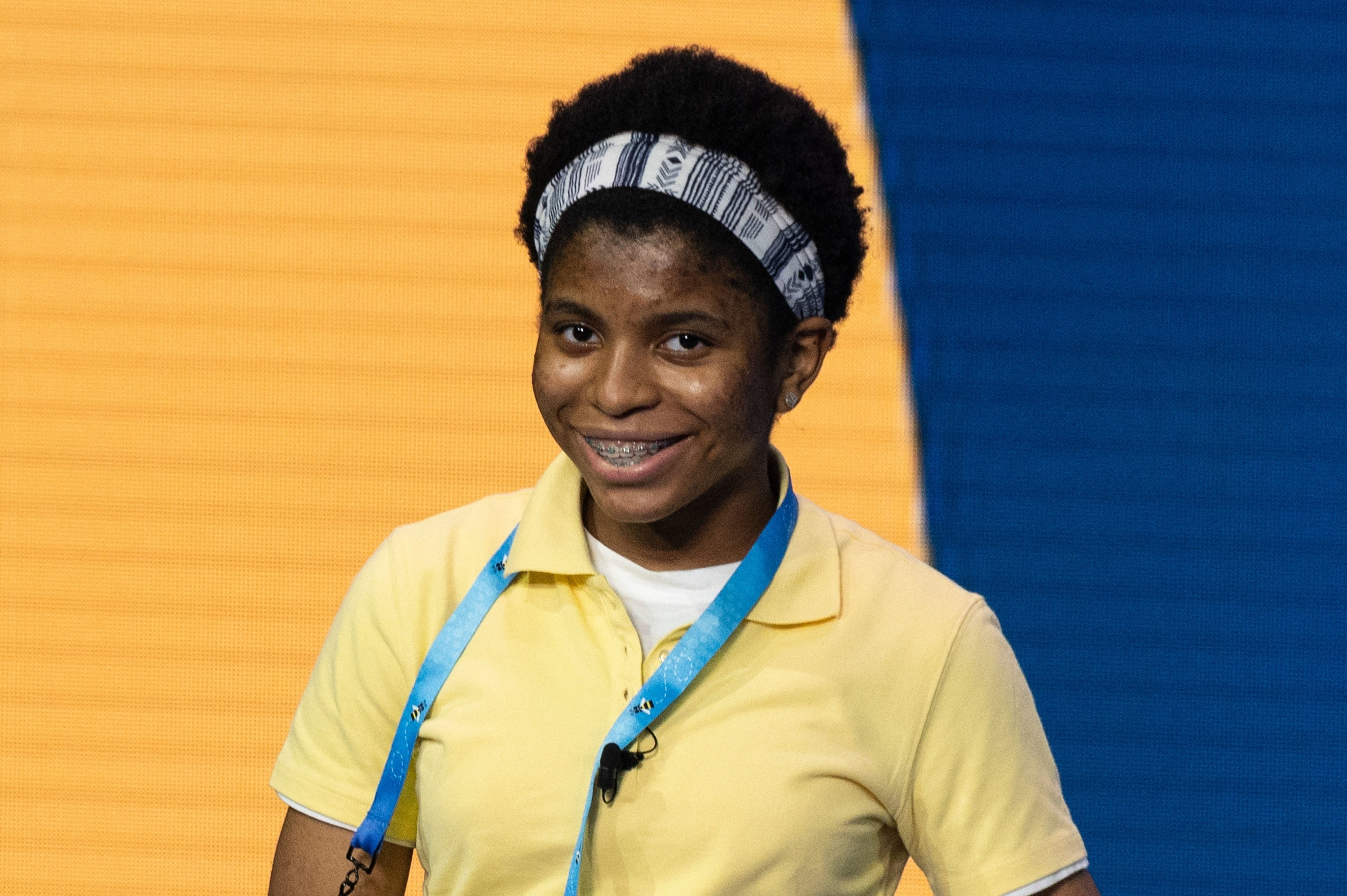 Photo of a smiling teenager with braces wearing a yellow polo shirt and a headband