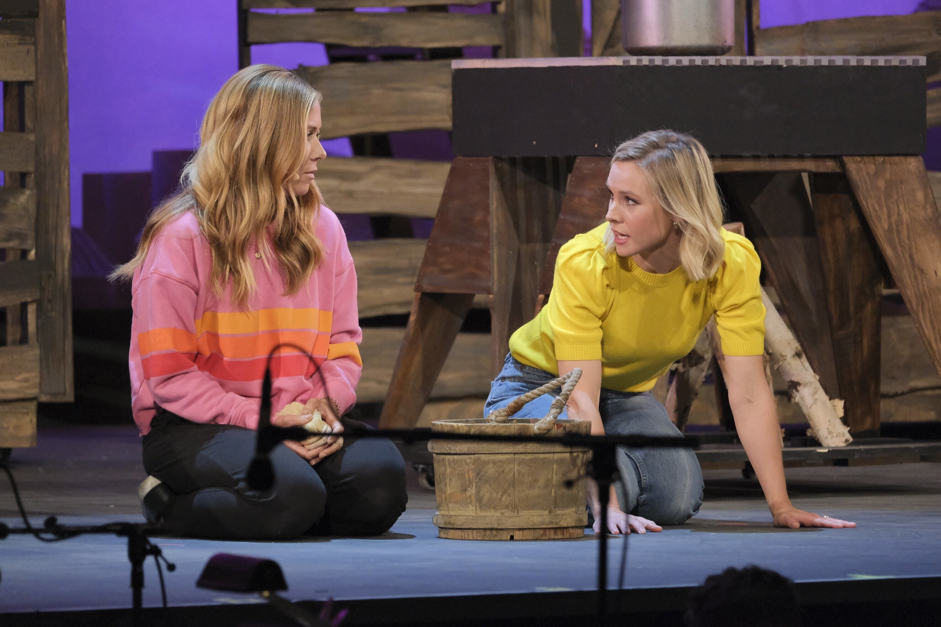 Kristen Bell onstage on her knees with another performer