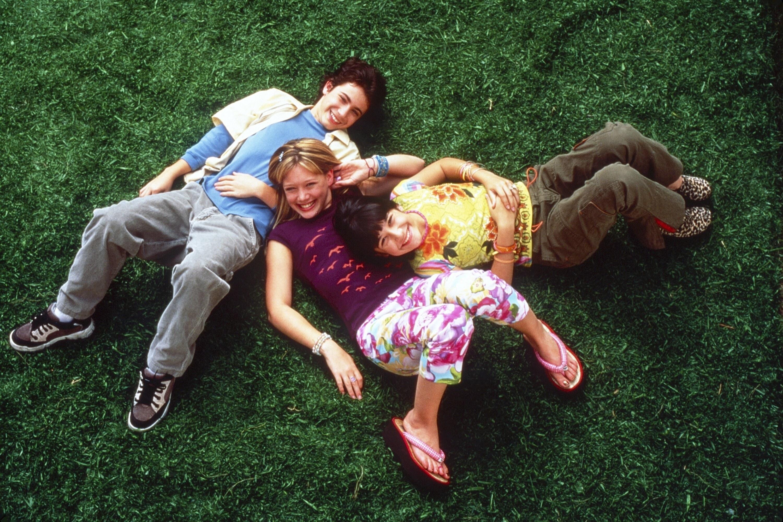 Adam Lamberg, Hilary Duff, and Lalaine lie on the grass