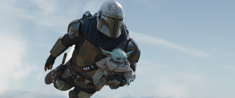 The Mandalorian flies through the air with Baby Yoda
