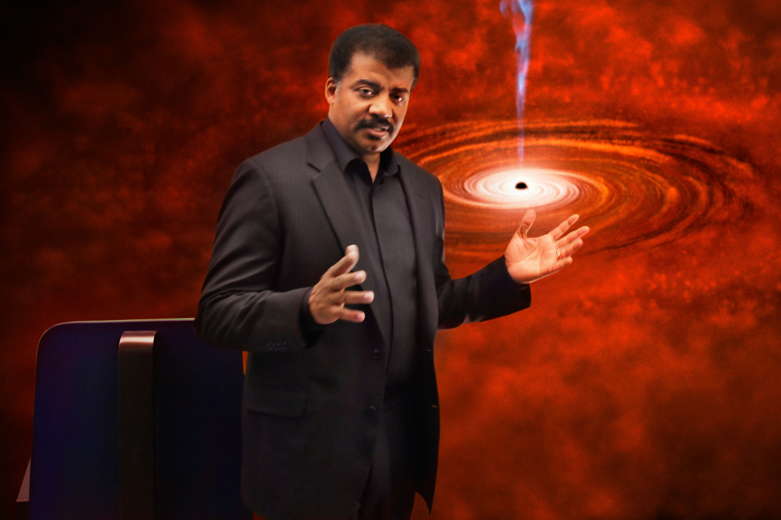 Neil dGrasse Tyson stands before a picture of outer space
