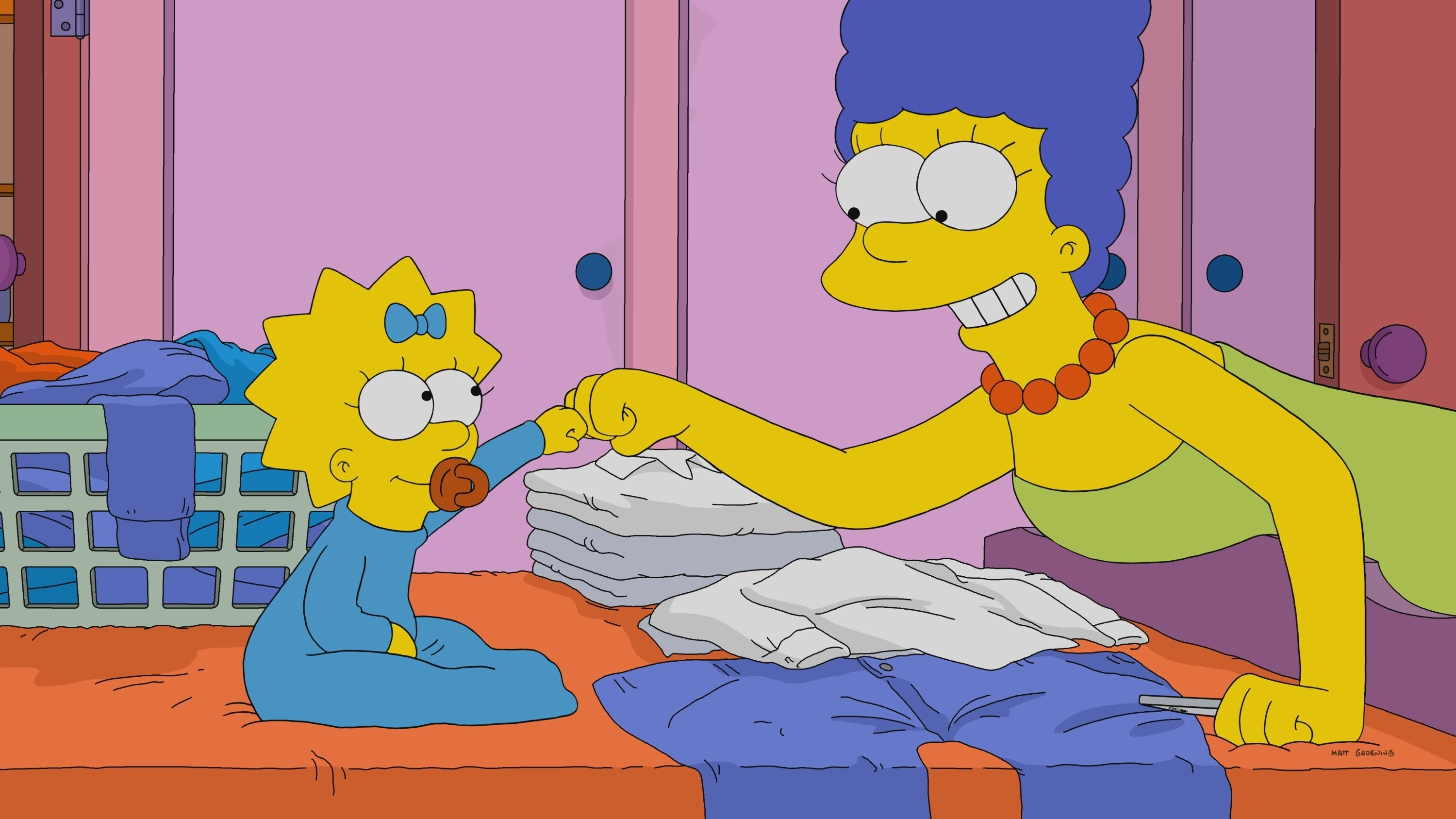 Marge and Maggie Simpson fist bump while folding laundry