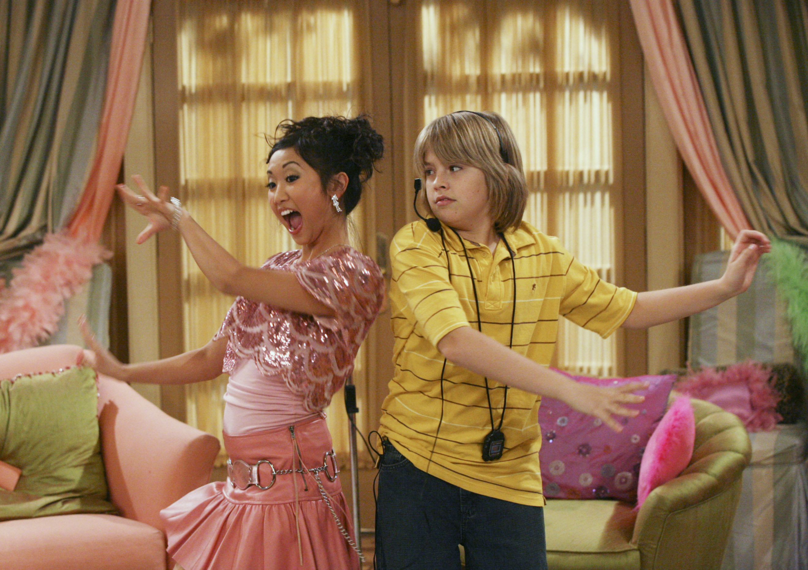 Brenda Song and Cole Sprouse stand in a hotel suite