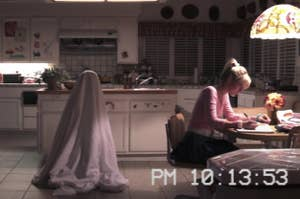 A figure in a sheet stands behind a girl sitting at a kitchen table