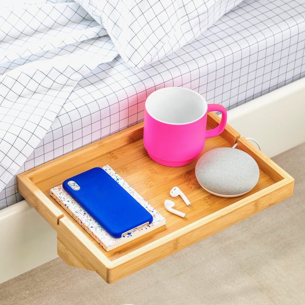 a small wooden shelf attached to the side of a bed