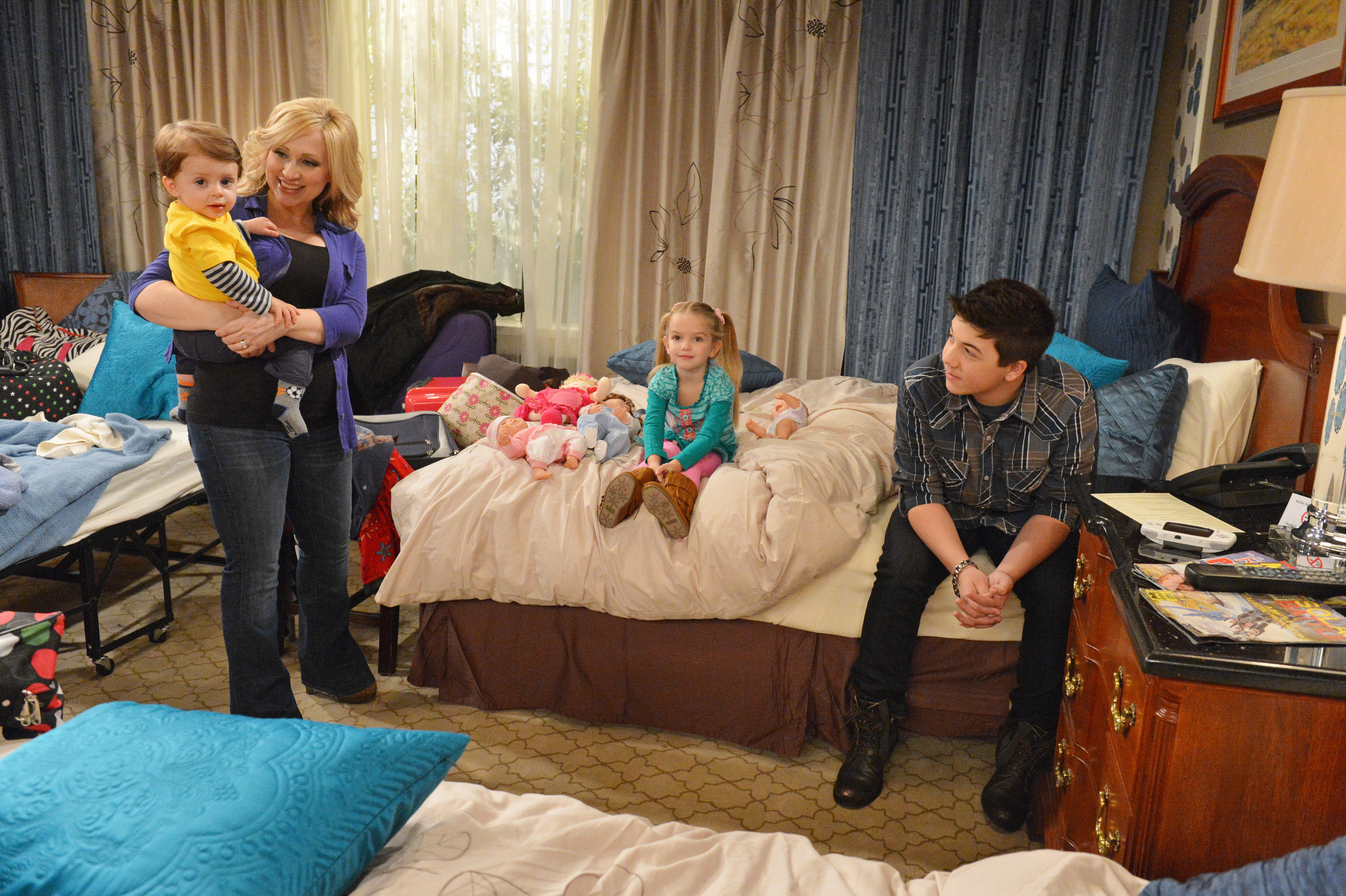 Leigh-Allyn Baker holds Logan Moreau while Mia Talerico and Bradley Steven Perry sit on a bed