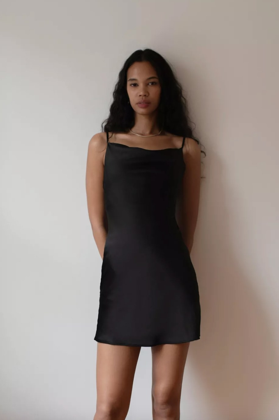 the cowl neck slip dress in black on a model