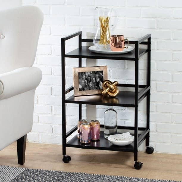 The 3-tier cart in black being used as a decorative side table
