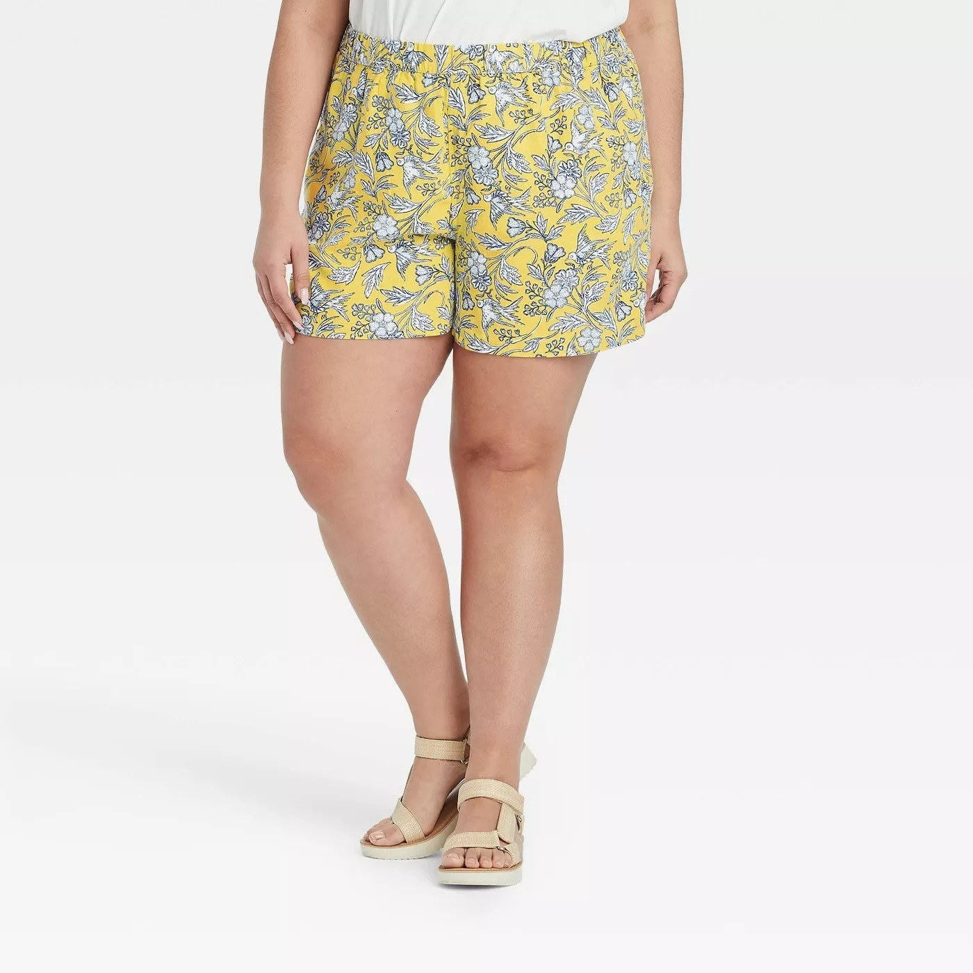 Model wearing floral patterned shorts in yellow, stops midthigh