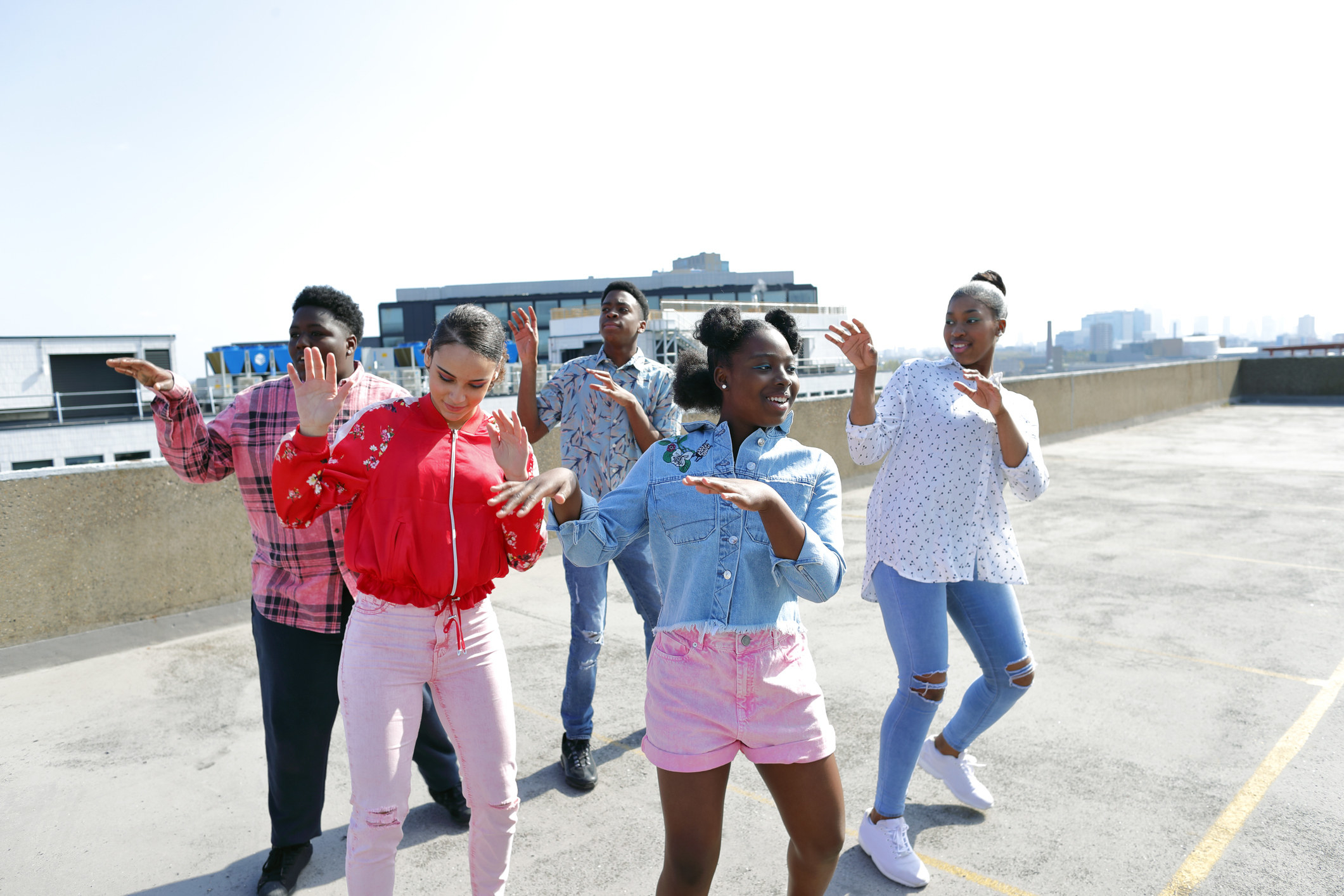 Young people dancing in a parking garage