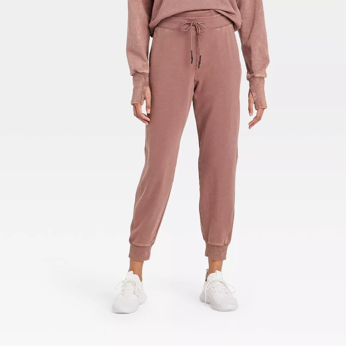 Model wearing light mocha sweats cuffed at the bottom of the pants, stops at the ankle