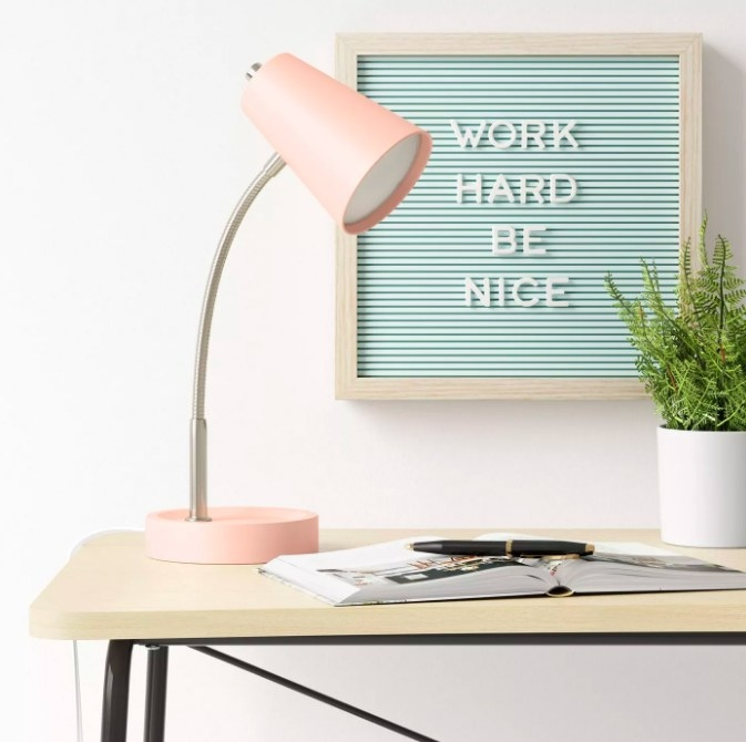"""The blue letterboard on the wall behind the desk with the message """"work hard be nice"""""""