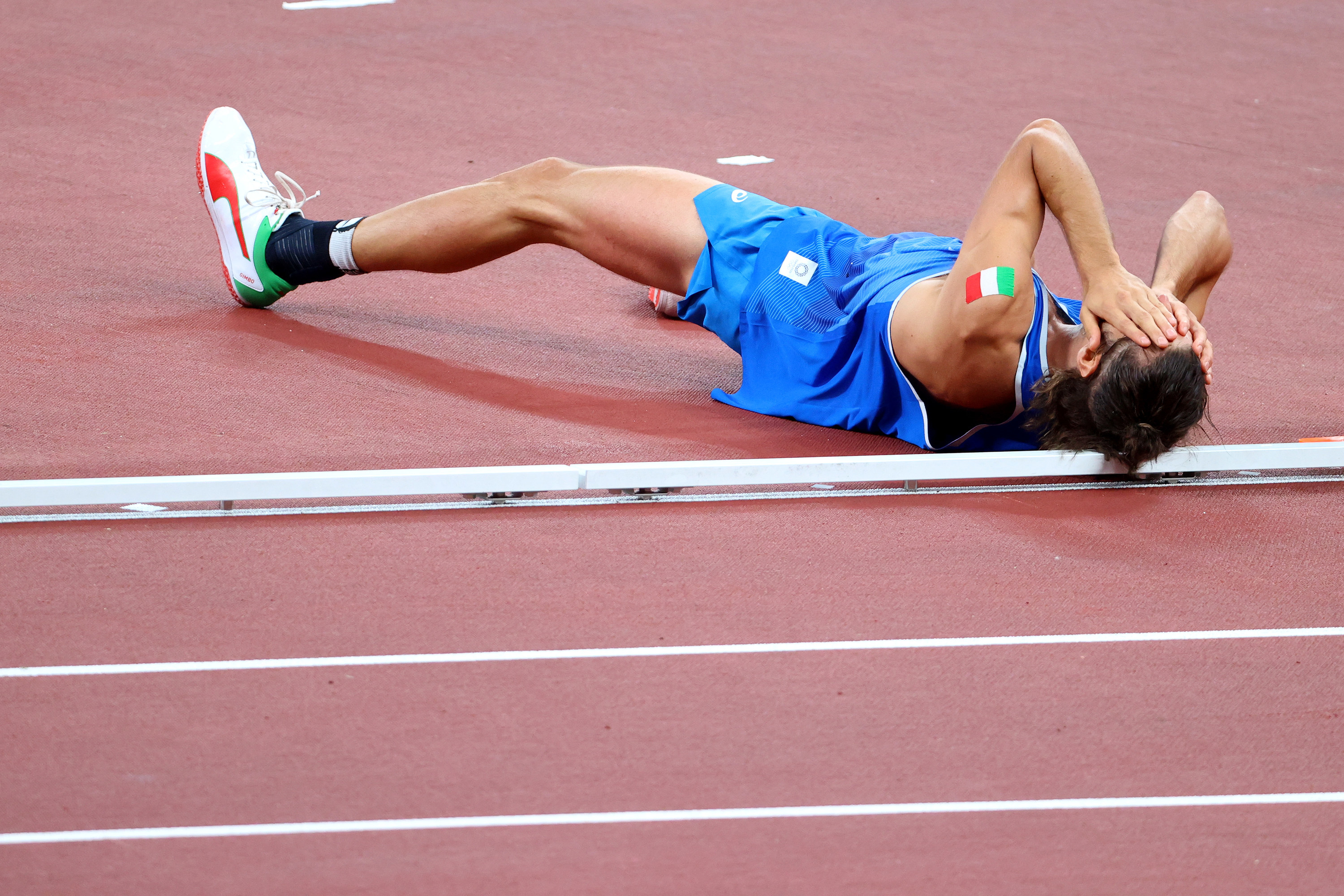 Tamberi lies on his back on the track and covers his eyes with his hands