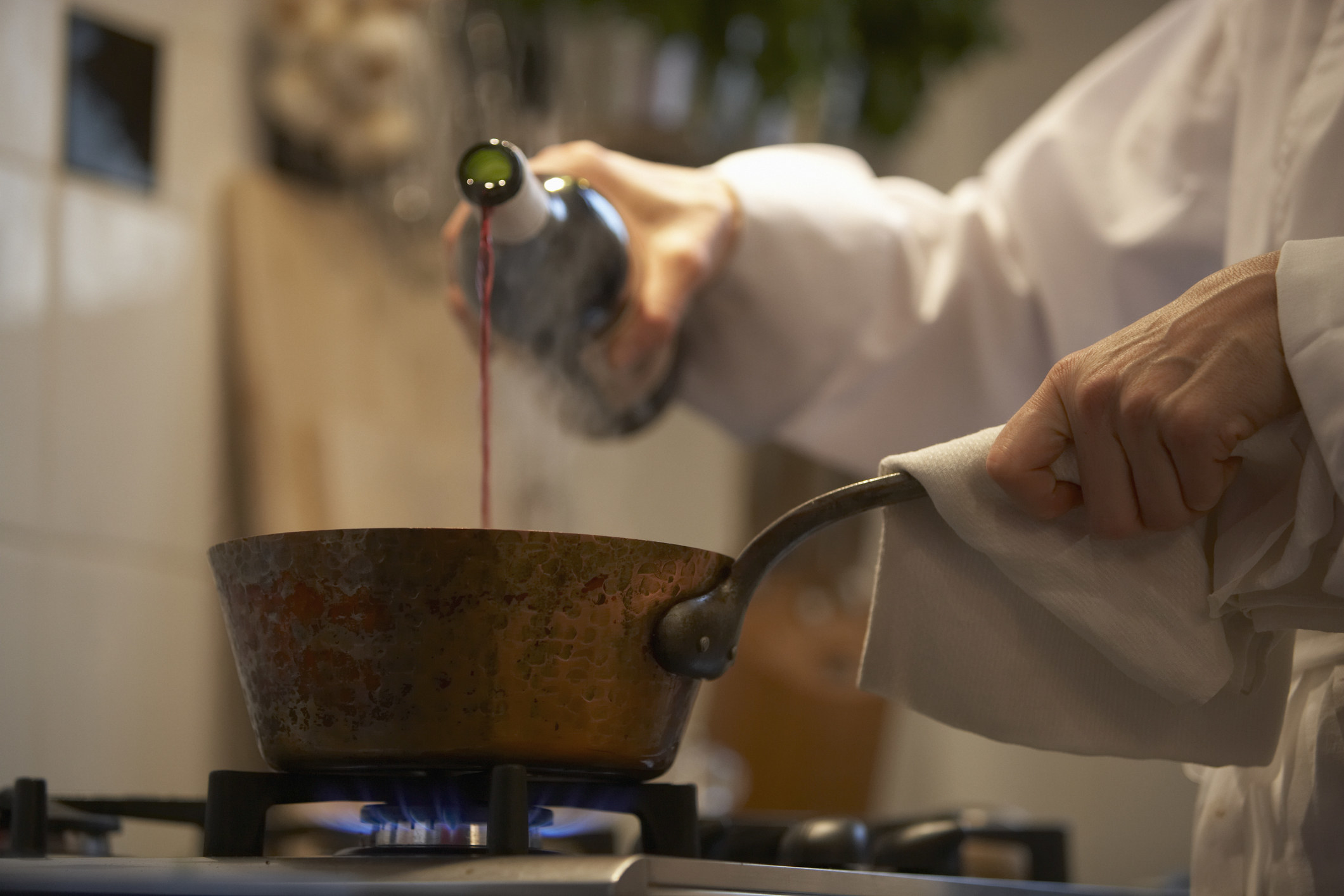 A chef pouring wine into a pot