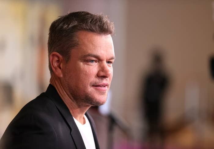 Damon looks in the distance at a red carpet event while wearing a suit and t-shirt