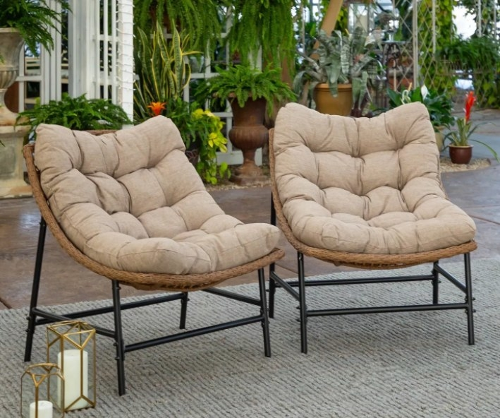 the two patio chairs with tan cushions on a patio