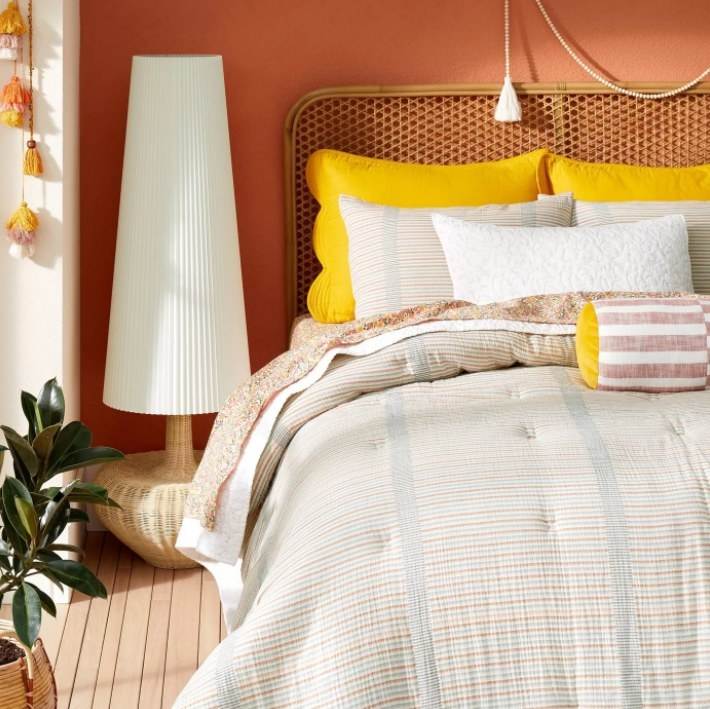 the striped comforter set on a bed with yellow pillows