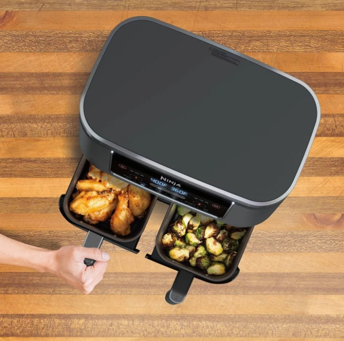an aerial view of the air fryer with chicken in one basket and veggies in the other