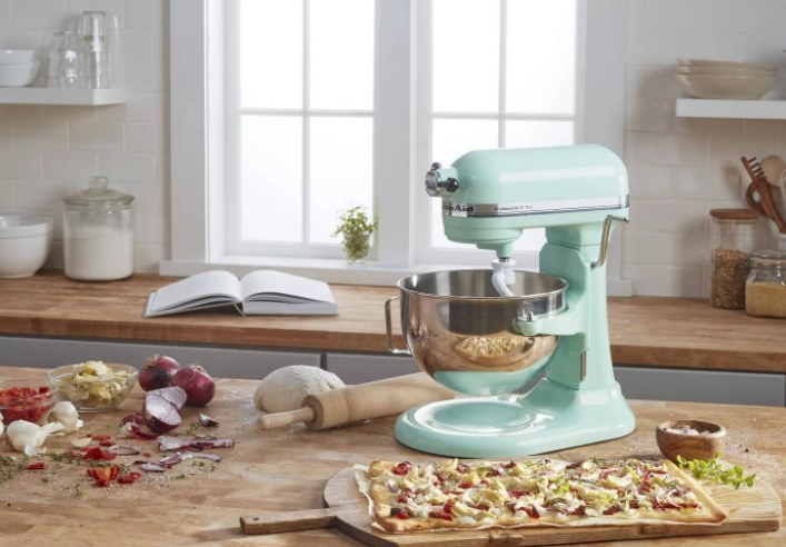 the blue mixer on a counter with ingredients and pizza next to it