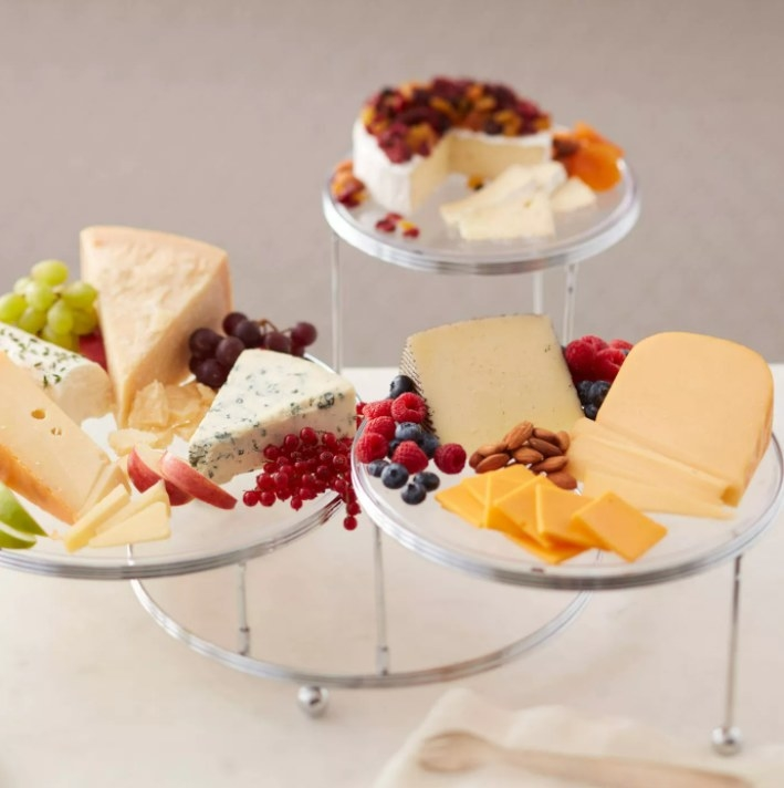 the 3-tier party stand with cheese and fruits on it