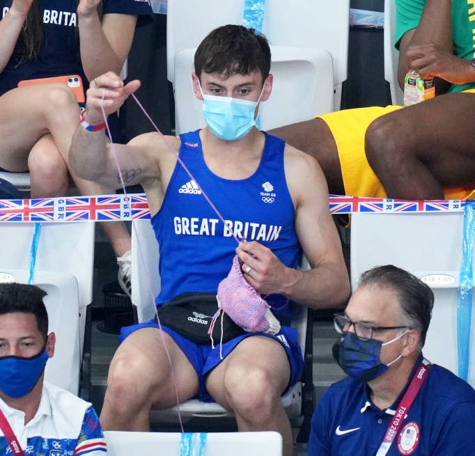 Tom Daley of Great Britain knits as he watches the Women's 3m Springboard Final