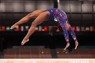 Simone Biles of Team United States competes in the Olympics, shown upside down midflip on a balance beam
