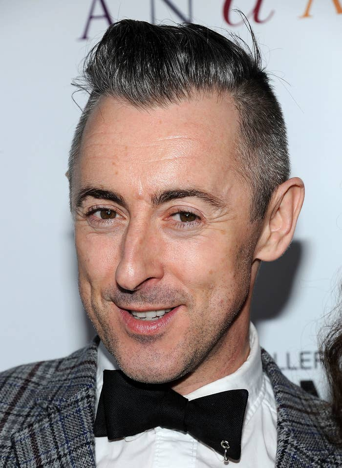 Alan Cumming poses for the camera at a red carpet event while wearing a bow tie, shirt, and jacket