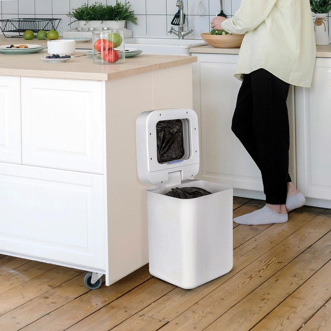 The open trash can next to a kitchen island