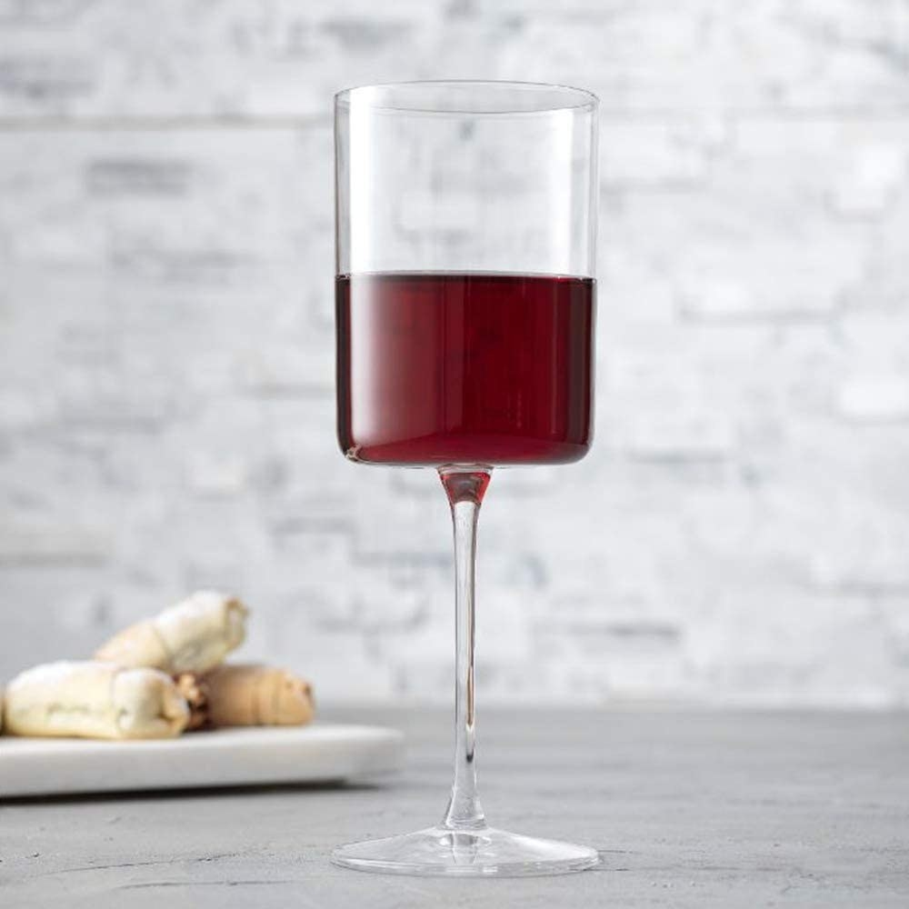 A glass filled with wine in front of a plate of appetizers