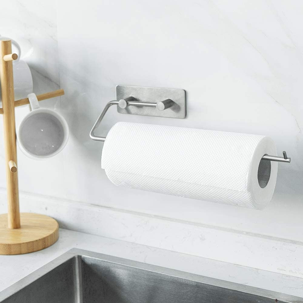A roll of paper towel on the rack above a sink