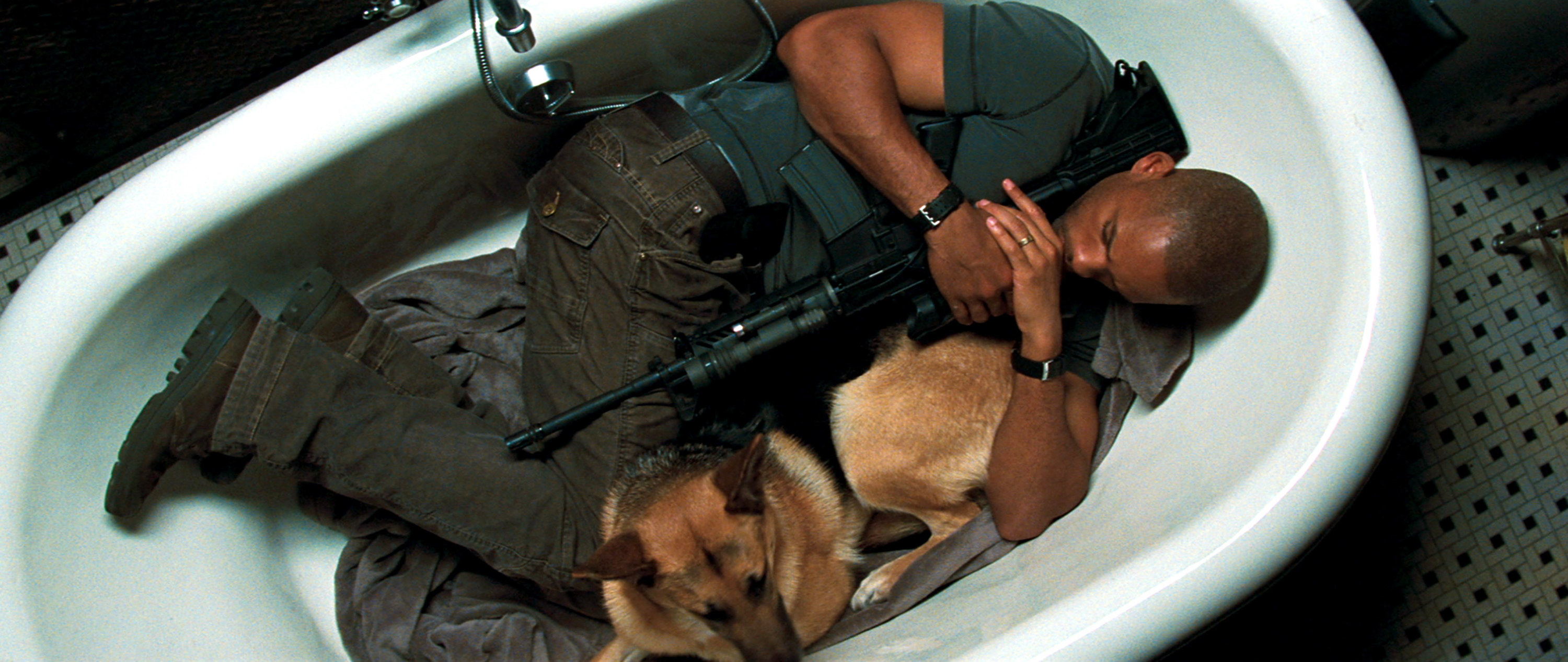 Dr. Neville clutching a gun while sleeping in a bathtub with his dog Sam
