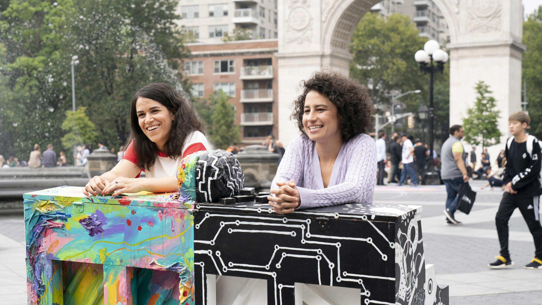 Abbi and Illana leaning on pianos in Washington Square Park