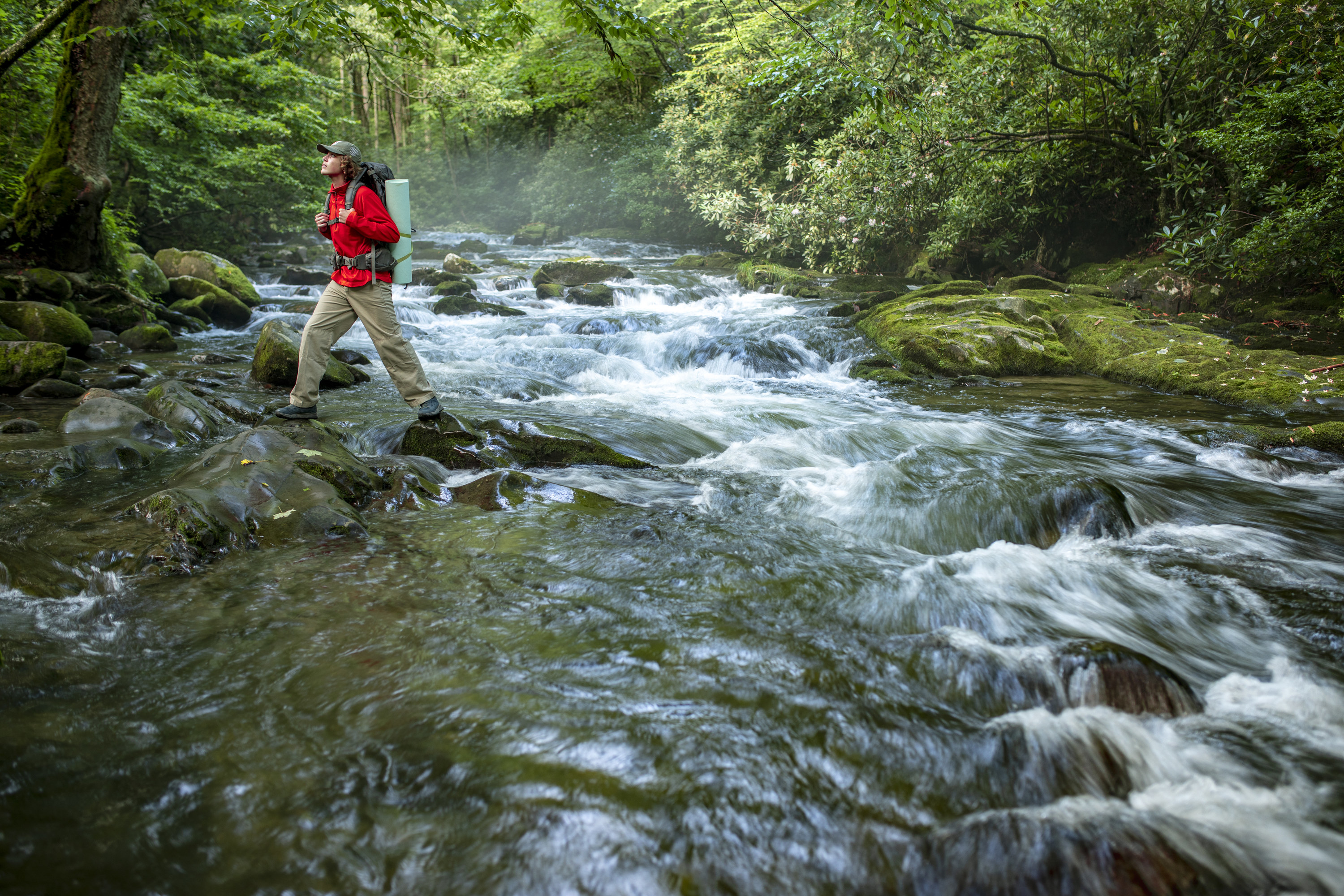 A hiker walks over the boulders that dot the roaring river in Great Smoky Mountains national park.