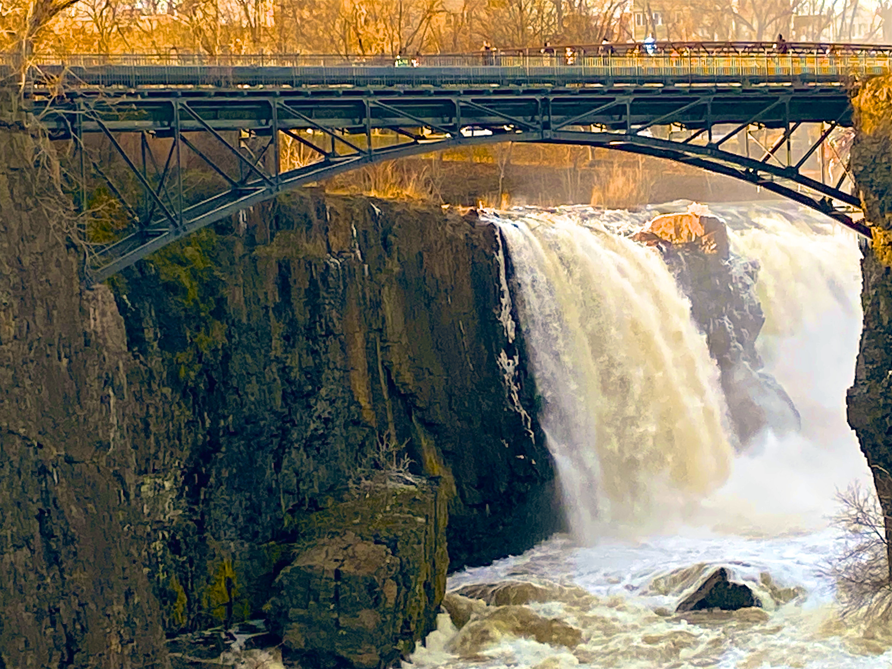 A waterfall thunders down into a river below, while a charming bridge lets visitors view from above.