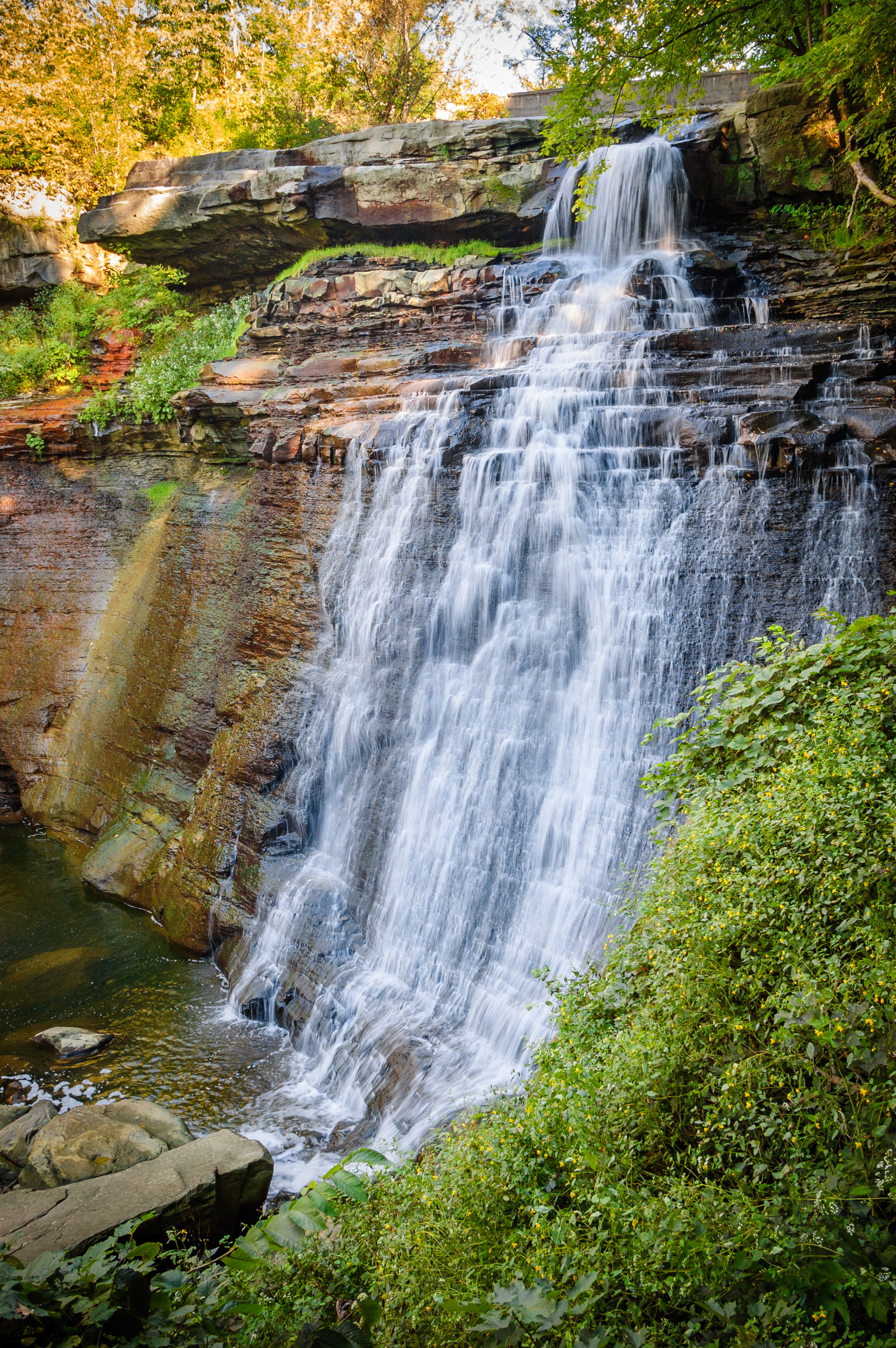 A tall waterfall rushes over a worn out rock formation, made up of flat layers of various thickness. Lush bushes and leaves surround the waterfall.