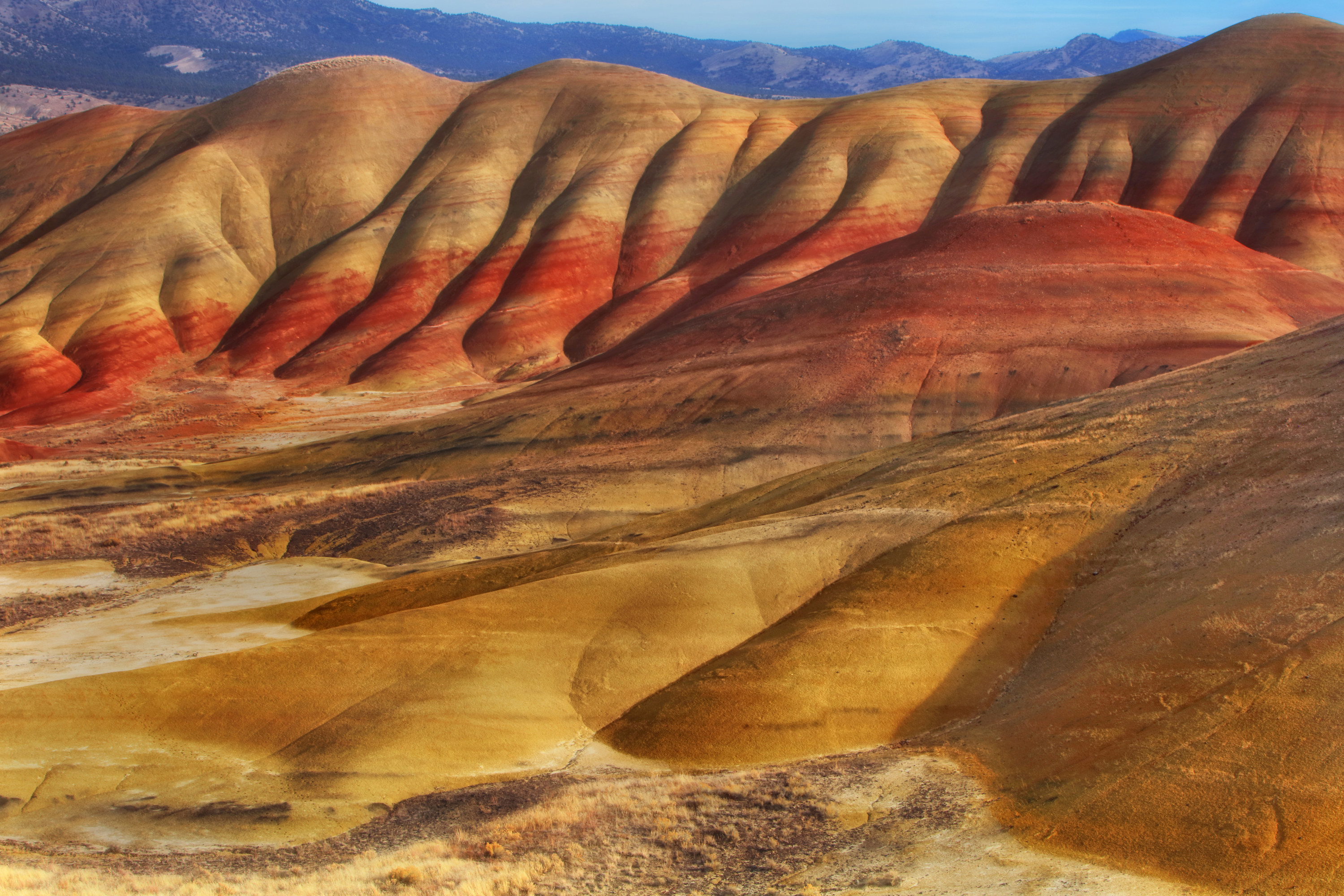 Voluptuous, curvy, indented mountains made up of multicolored sedimentary layers accentuate the John Day Fossil Beds.