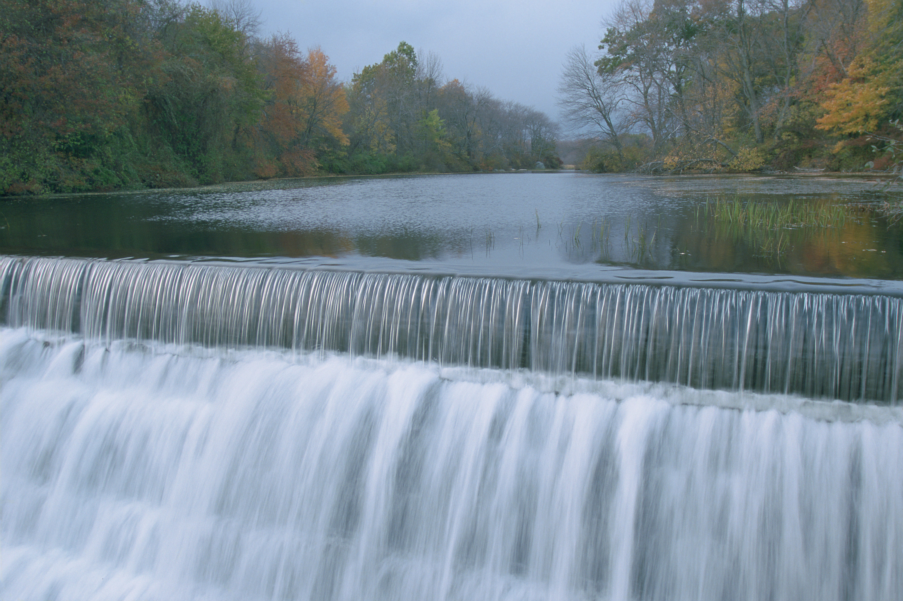 A close-up of a perfectly straight waterfall coursing down. Autumn foliage dresses up the trees behind.