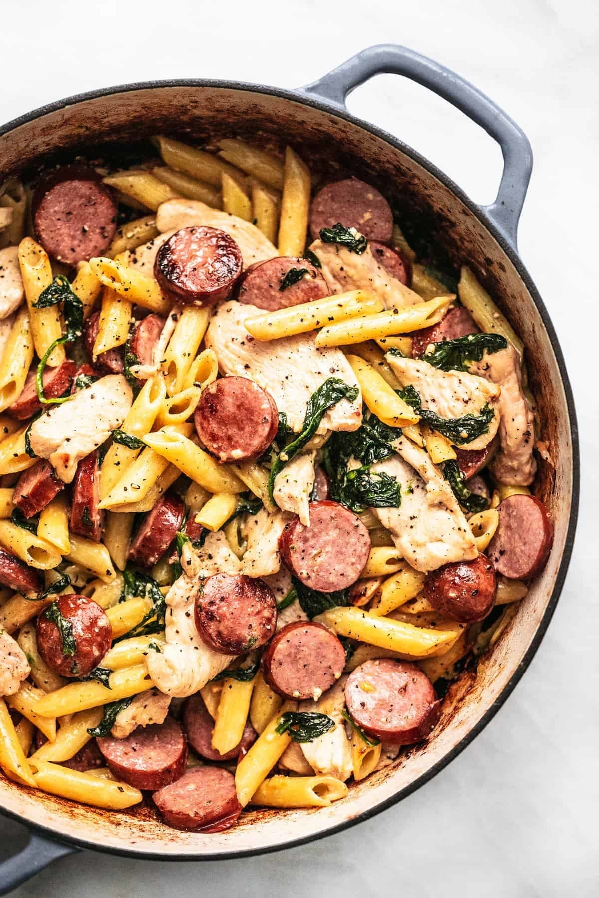 A pot of creamy pasta with chicken and sausage