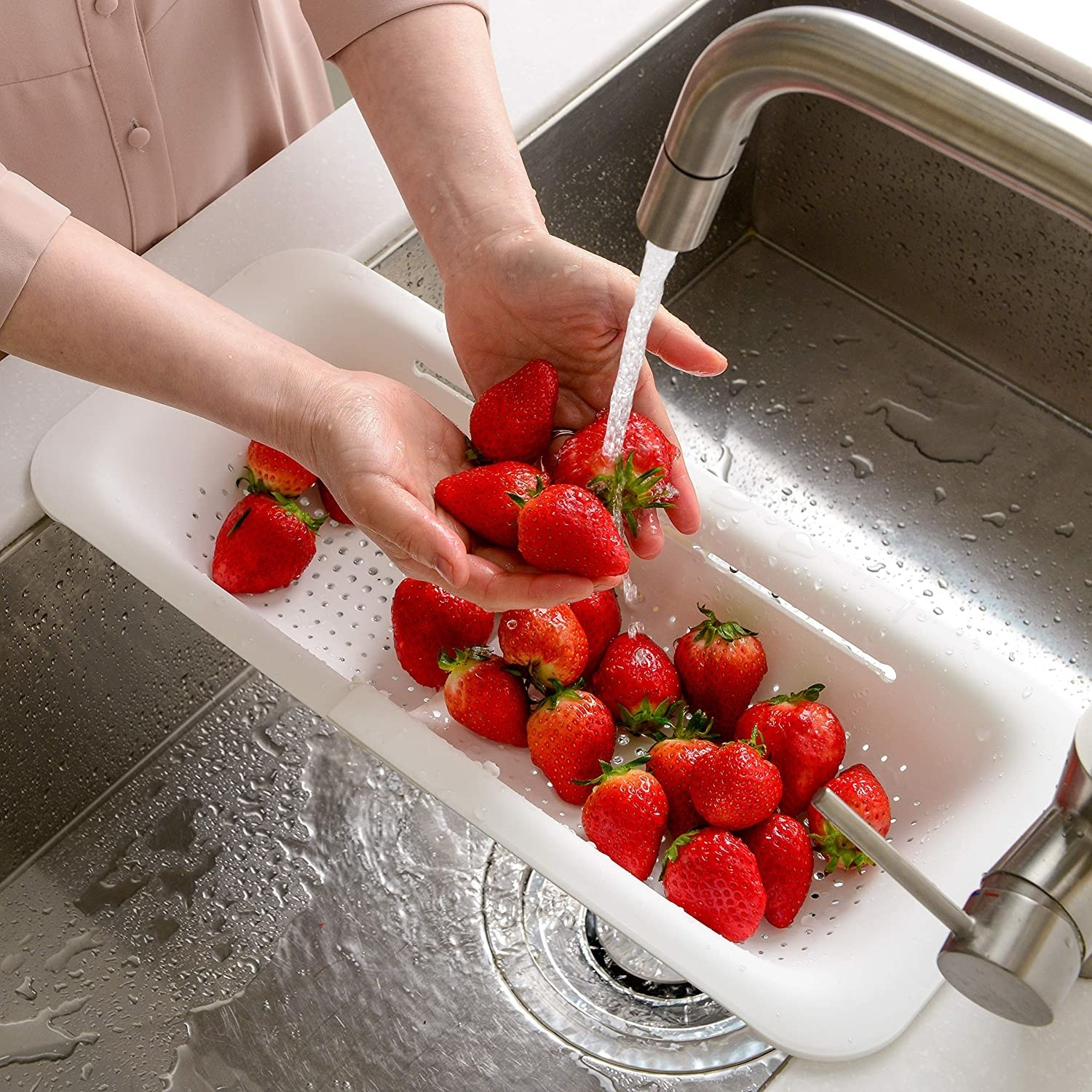 A person washing strawberries in the colander