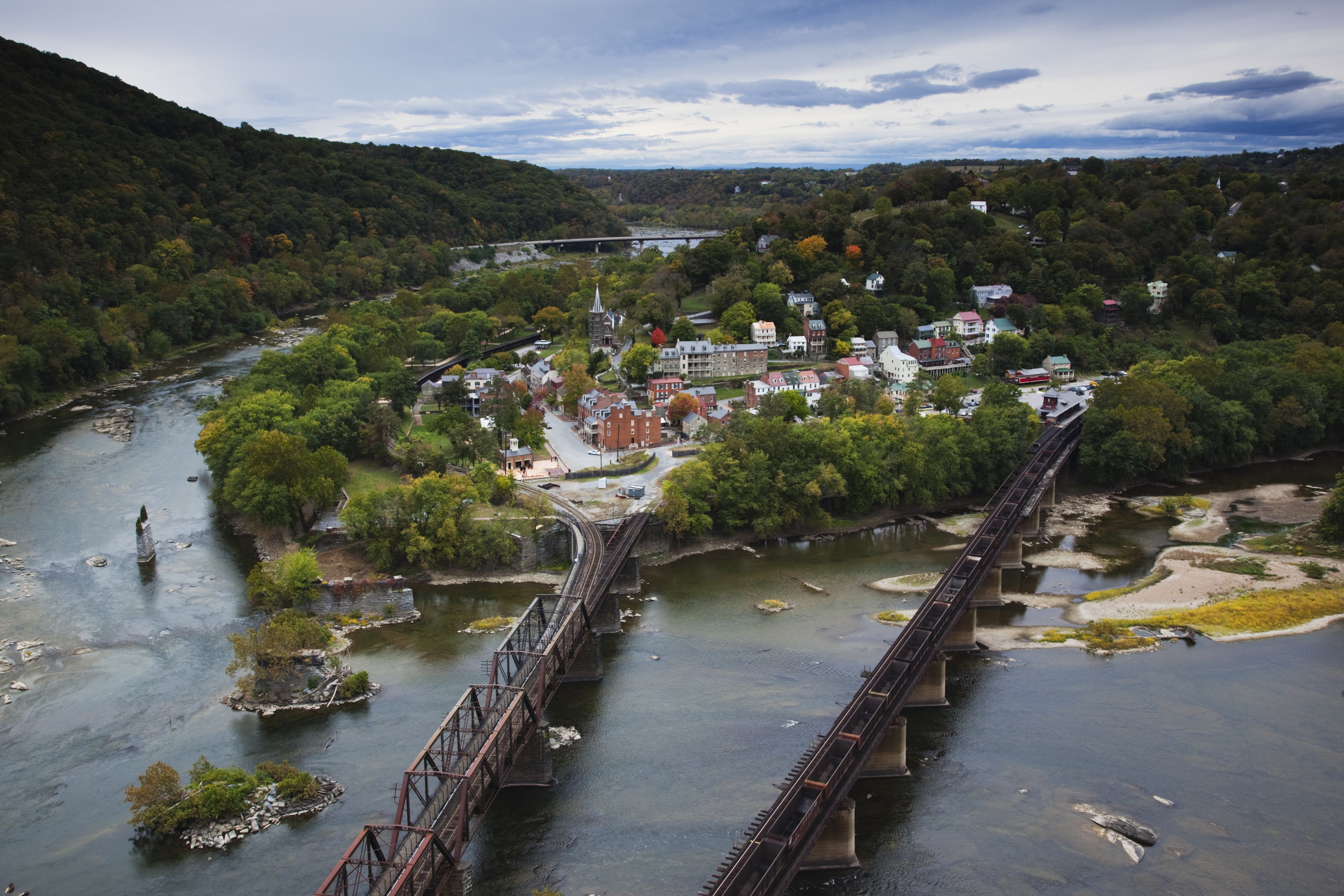An aerial shot of Harpers Ferry that shows off the two bridges, charming buildings, and the surrounding green areas.