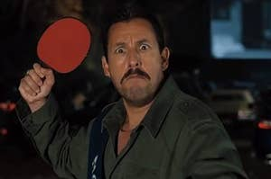 hubie holds a table tennis paddle up, frowning with eyes wide