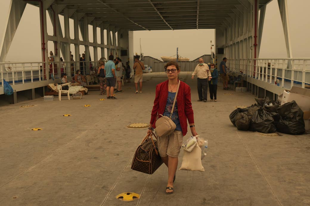 A woman walks off a boat carrying bags full of personal belongings