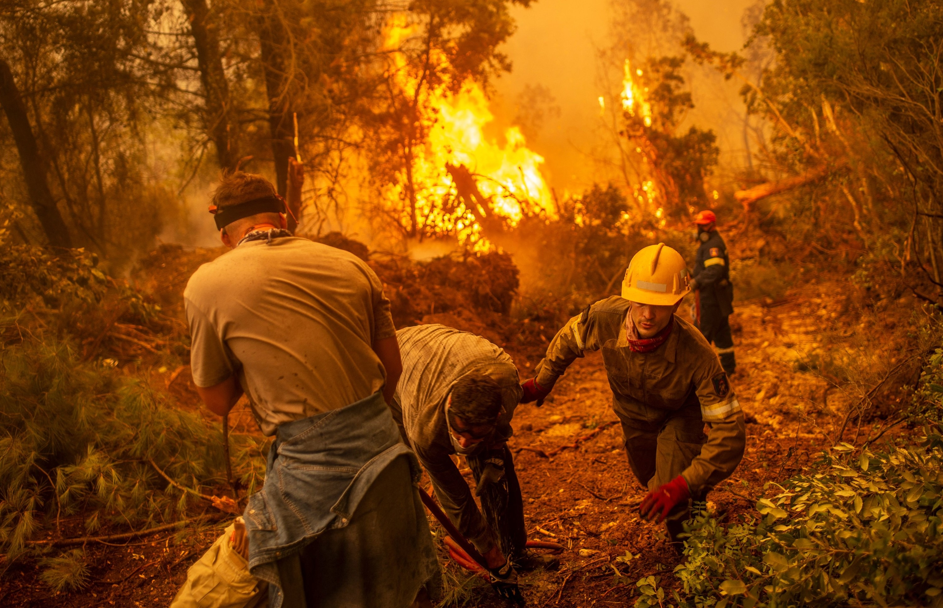 Volunteers stand by a firefighter near massive flames in the background