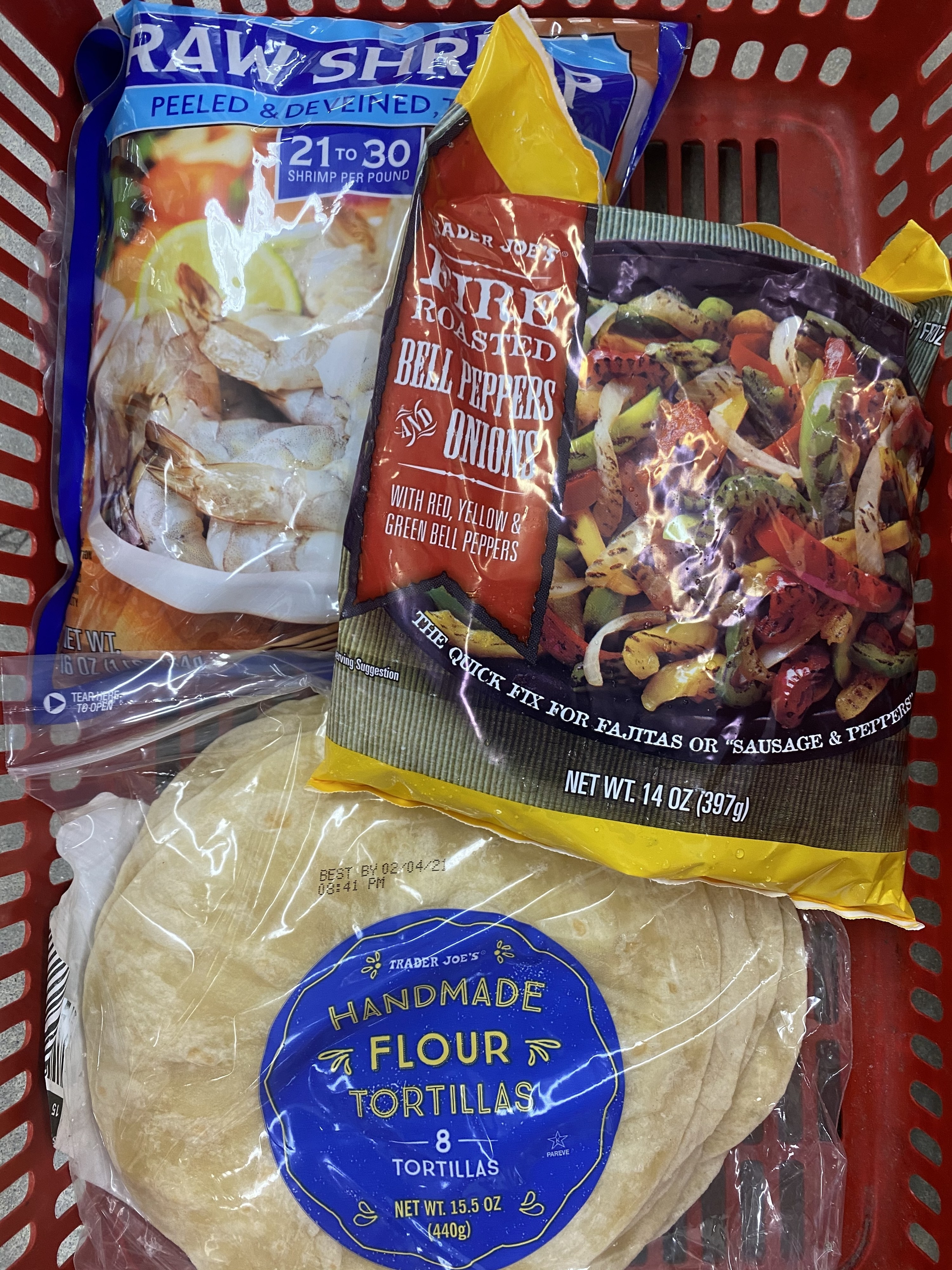 Frozen shrimp, pepper and onion medley, and flour tortillas in a grocery basket