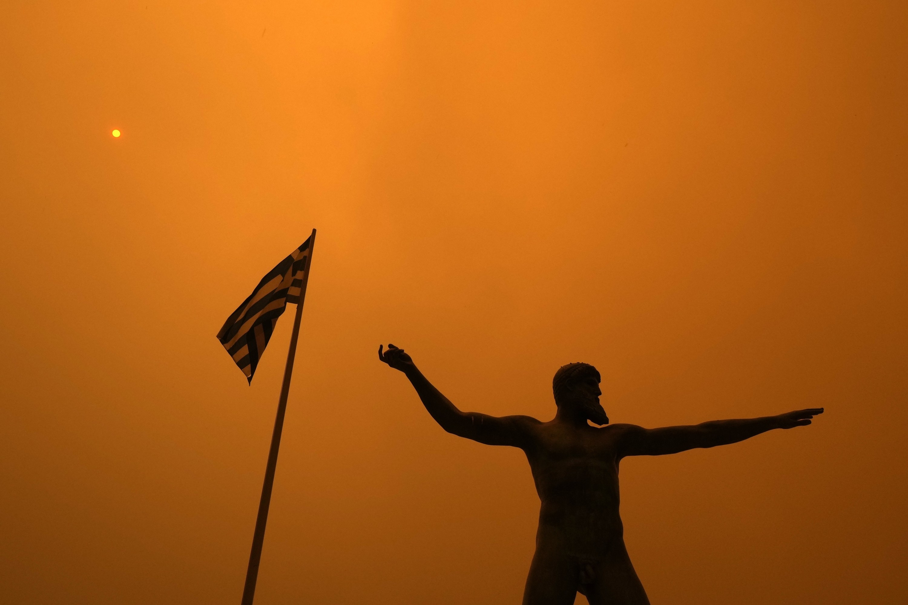 A sculpture of a Greek god stands beside a Greek flag, both silhouetted against a hazy sky
