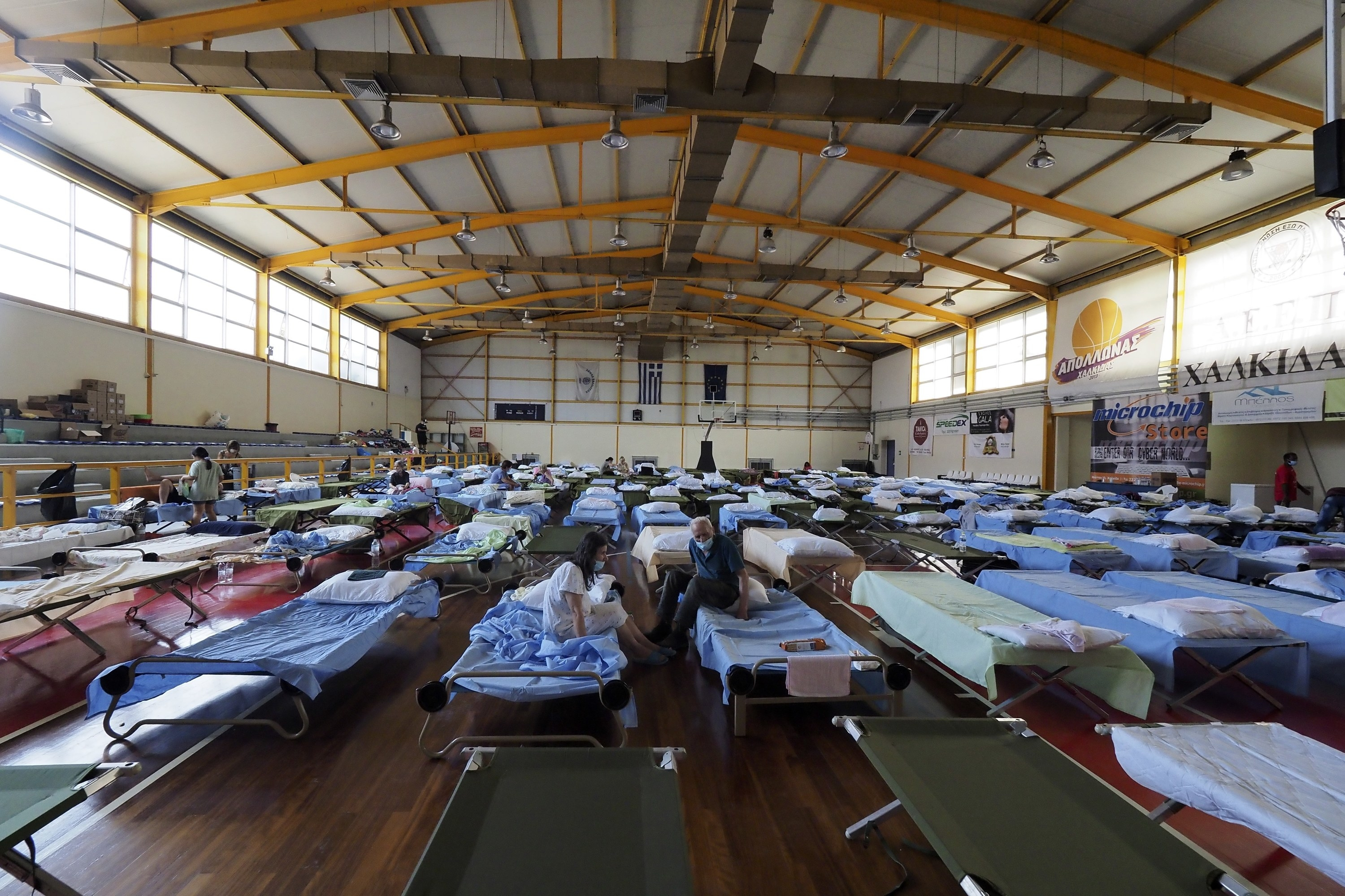 A temporary shelter in a basketball court has cots and temporary beds set up, wall to wall