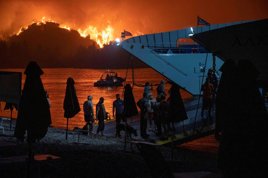 Passengers board a ferry at night as a fire burns on the horizon