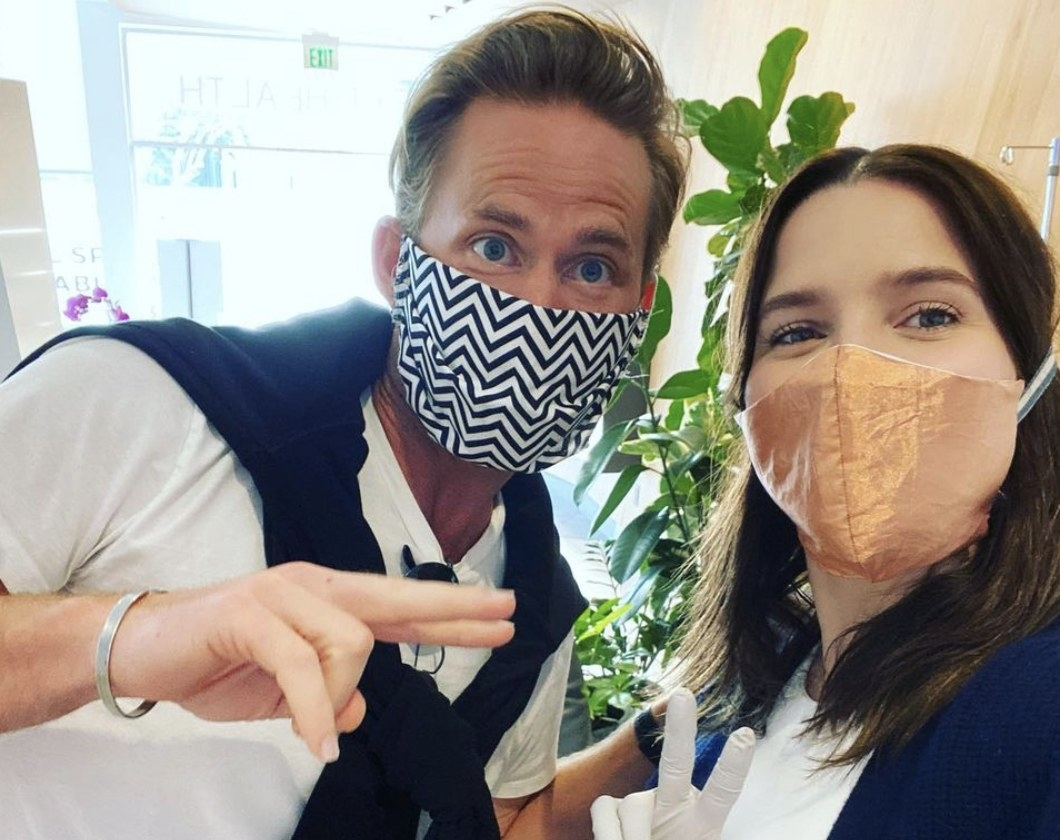 Sophia and Grant pose while wearing masks in a COVID test center