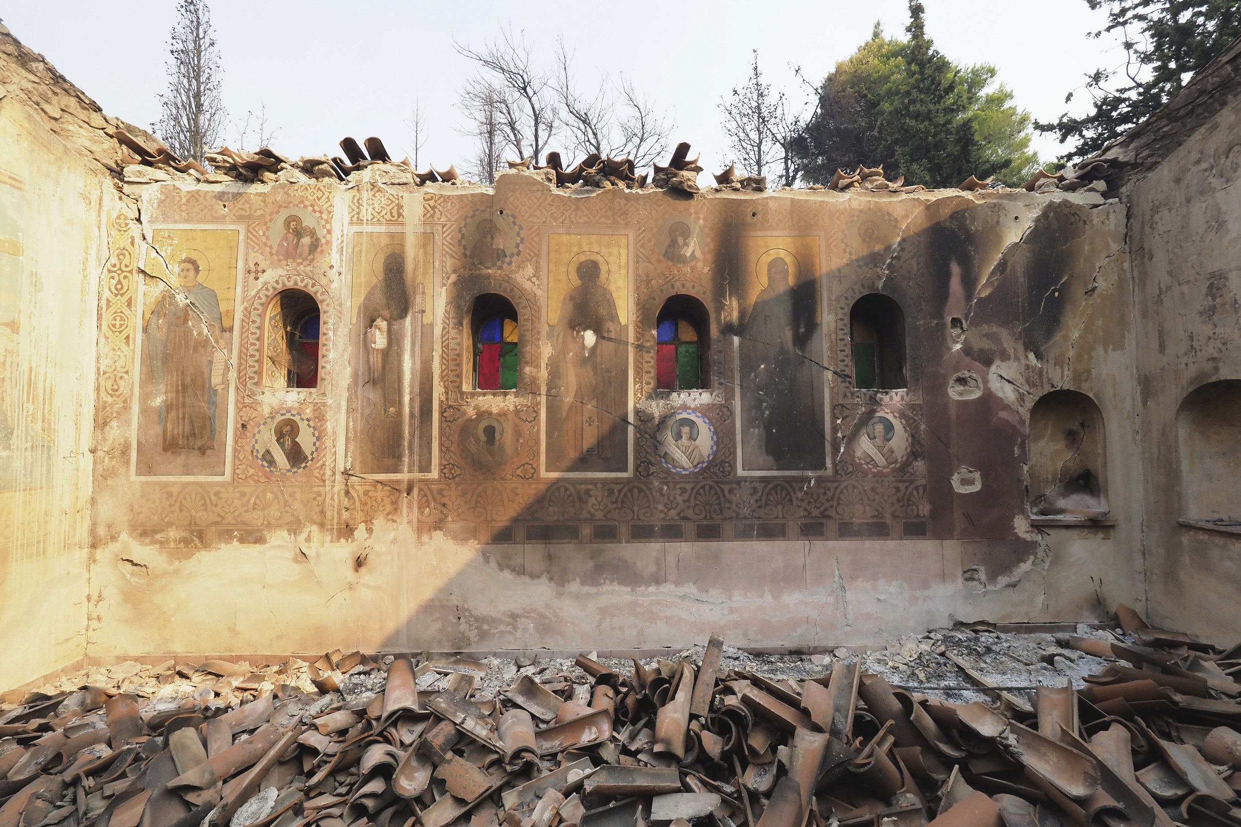 A church's wall, decorated with images of saints, is cracked and charred, surrounded by debris, after a wildfire