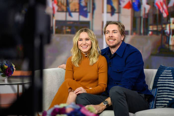 Kristen Bell and Dax Shepard smiling as they sit on a couch during filming